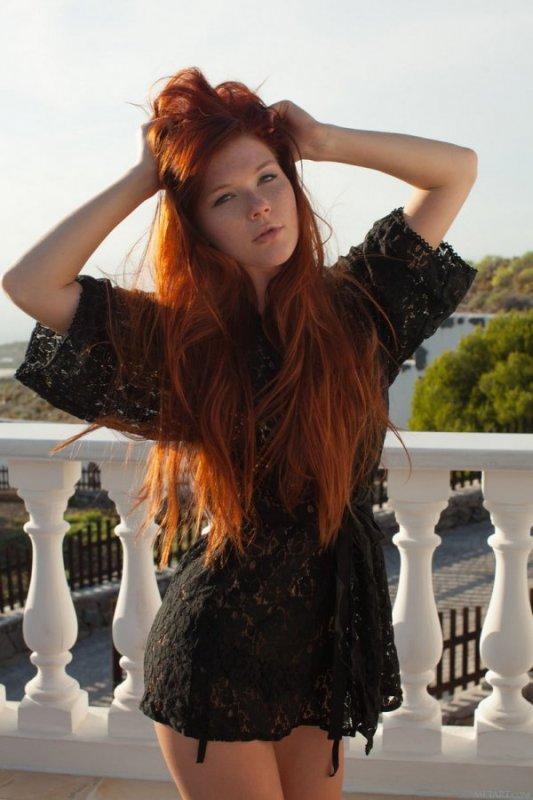Рыжая девушка сняла черное платье оголив тело