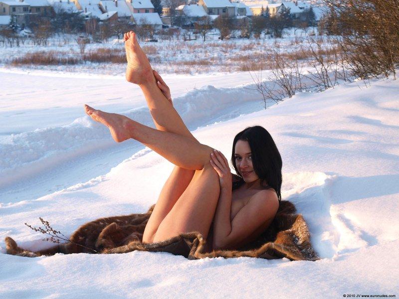 Голая девушка позирует на снегу